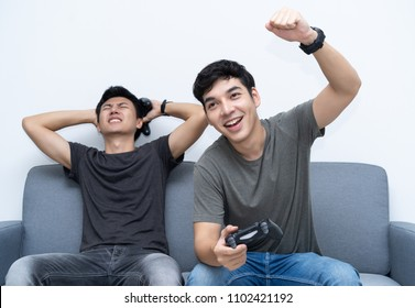 Friends and video games. Two young men gamer playing video games while sitting on sofa. One guy is celebrating winning.