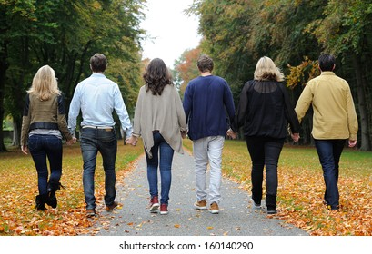 Friends walking in forest during autumn