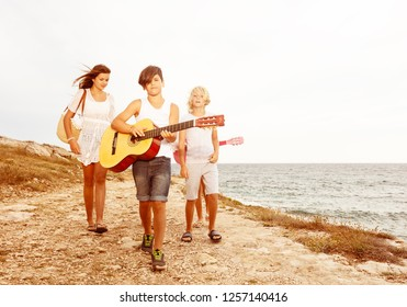 Friends walking on the beach and playing guitar