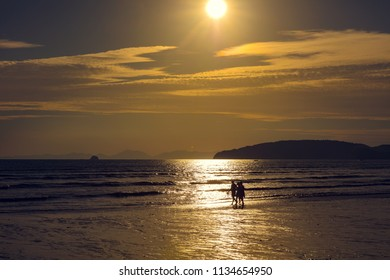 Friends Walking On Shore At Beach During Sunset