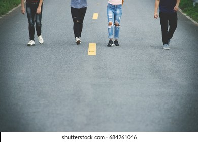 Friends walking together on long straight road,Friendship concept,Vignette effect