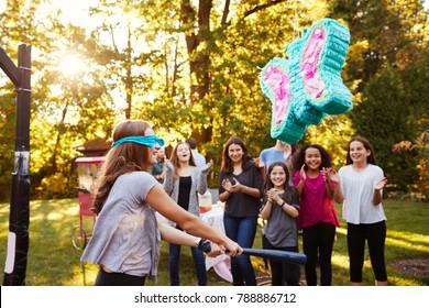 Friends watch pre-teen girl hitting a piâ??ata on her birthday
