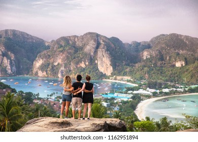Friends watch the sun rise over a town on Phi Phi islands. The cliff top viewpoint also reveals mountains and beaches.