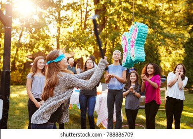 Friends watch teenage girl hitting a piâ??ata on her birthday