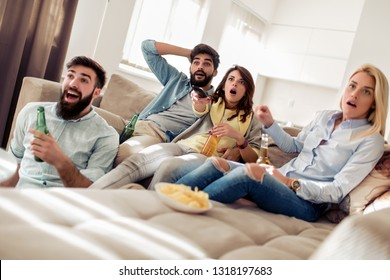 Friends watching football game at home.