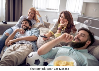 Friends watching football game on tv,having great time together.