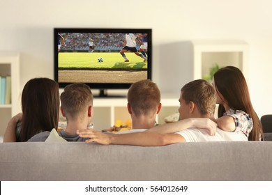 Friends watching football game on television at home. Leisure and entertainment concept.
