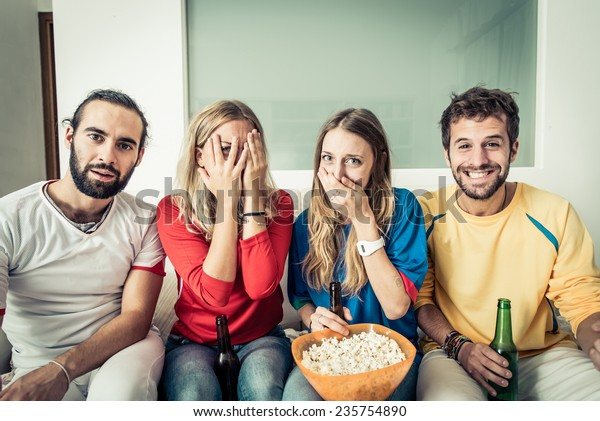 friends watching horror movie at television. different reaction on their faces