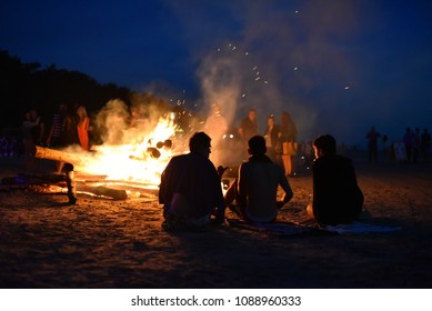 Friends watching a large fire on the sand beach of Baltic sea in the town of Jurmala during celebration of midsummer holidays (Ligo) in Latvia.