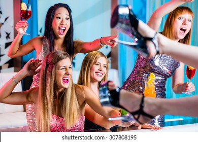 Friends watching striptease in strip club grabbing at female stripper