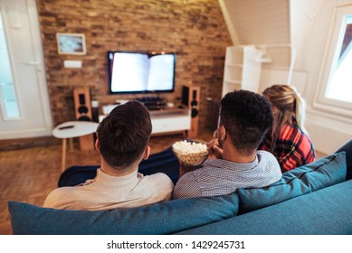 Friends watching tv and eating popcorn, rear view.