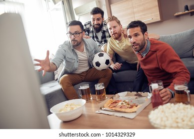 Friends watching TV at home while eating pizza and drinking some cold beer.