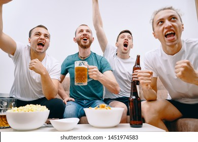 Friends watching Tv at home while eating chips popcorn and drinking some cold beer