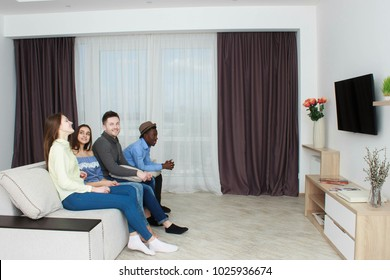 friends watching tv, friends in living room, company sitting on couch and watching television, wide angle.
