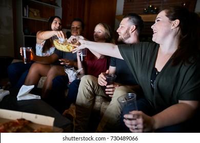 friends watching tv at night passing around snacks