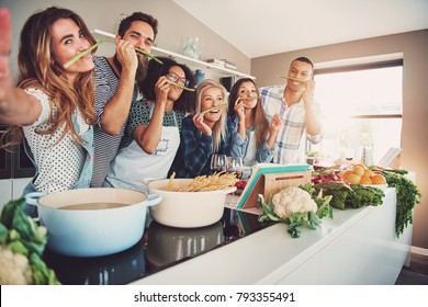 Friends wearing asparagus stalks under their noses while standing in front of table full of pots, pasta noodles and vegetables