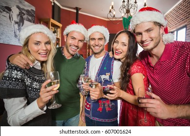 Friends wearing Christmas hats smiling at camera and holding wine glasses