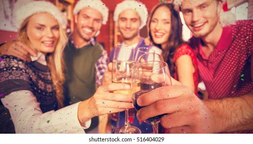 Friends wearing Christmas hats while toasting against flying colours