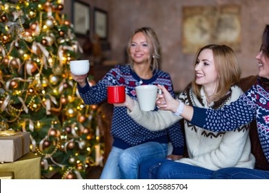 Friends wearing jerseys clinking coffee cups while having a home party in a loft. Decorated Christmas tree on a background