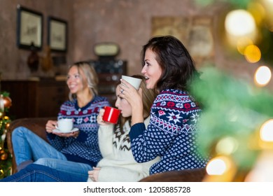 Friends wearing jerseys drinking coffee while sitting on a couch in a loft