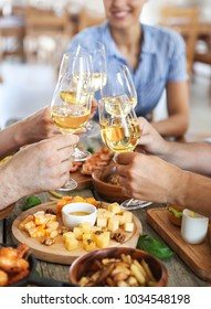 Friends with white wine toasting over served table with food. Friendship and happiness concept