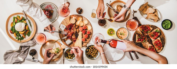 Friends wine and snacks party. Flay-lay of rose wine in glasses, cheese, fruit, meat, tomato brushettas, buratta salad and peoples hands over white table background, top view. Wine tasting concept