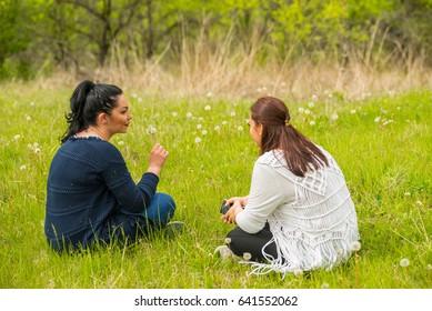 Friends woman in nature sitting on grass and blowing dandelions