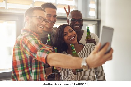 Friends at work taking self portrait with camera phone while holding green glass bottles of beer in office party