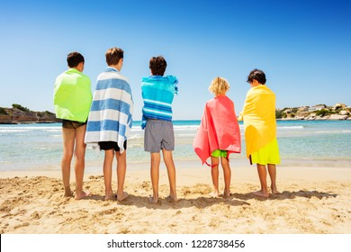 Friends wrapped in beach towels admiring seascape