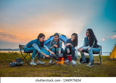 Friends of Young Asian women camping and cooking picnic together happy on weekend at sunset.