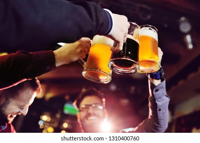 friends - young cute men drink beer in a bar, ringing glasses, smiling, laughing and talking. Bachelor party, Oktoberfest