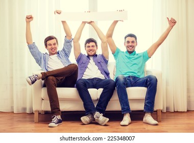 friendship and advertising concept - smiling male friends holding white blank banner