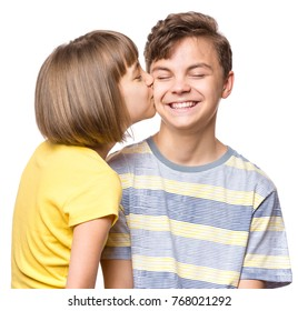 Friendship - beautiful girl kissing teen boy. Portrait of happy brother and sister, isolated on white background. Funny couple children - first love.
