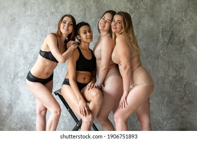 friendship, beauty, body positive and people concept - group of happy women different in underwear over gray background