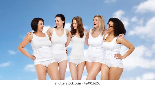 friendship, beauty, body positive and people concept - group of happy different size women in white underwear over blue sky and clouds background