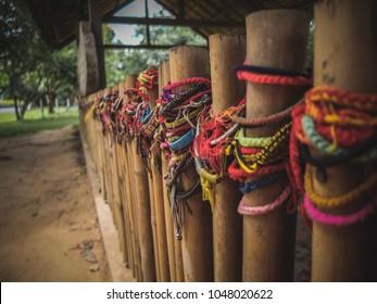Friendship bracelets left on wooden poles to pay respects. Killing Fields Mass Grave, Phnom Penh, Cambodia
