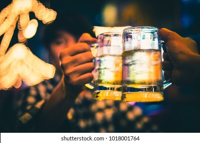 friendship and celebration concept - happy male friends drinking beer and clinking glasses at bar or pub