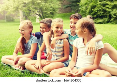 friendship, childhood, leisure and people concept - group of happy kids or friends sitting on grass in summer park