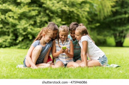 friendship, childhood, technology and people concept - group of happy kids or friends with smartphone in summer park