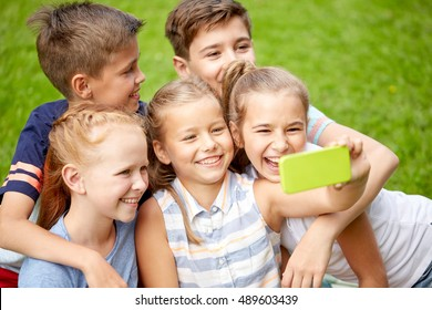 friendship, childhood, technology and people concept - group of happy kids or friends taking selfie by smartphone in summer park