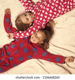Friendship. Comfort, home concept. Girl sisters in pajamas happy smile in bed, top view. Children nightwear fashion. Bedtime, slumber, dream, sleepover. Childhood, family, love, friendship.