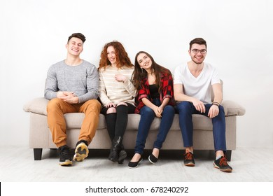 Friendship, communication, party time - cheerful friends talking, having fun, sitting on couch indoors and laughing