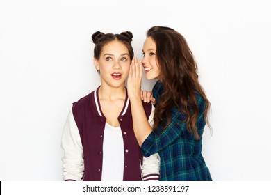 friendship, communication and people concept - happy teenage girls gossiping or sharing secrets over white background
