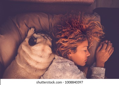 friendship concepts for 40s woman sleeping with her best firends pug dog at home. Both on the pillow and brown warm tones. Dreaming together.