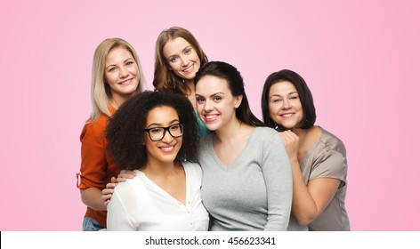 friendship, fashion, body positive, diverse and people concept - group of happy different women in casual clothes over pink background