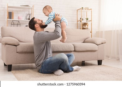 Friendship of father and son. Man and little boy looking at each other, baby grabs daddy's beard, sitting on floor at home, copy space