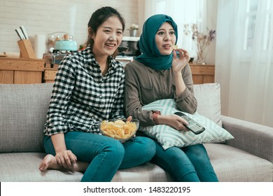 friendship food and leisure lifestyle concept. smiling asian girl friends with potato chips at home. happy japanese and islam ladies sitting on sofa watching comedy on tv in bright apartment day time