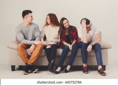 Friendship, fun, party time - cheerful friends talking, communicate, sitting on couch indoors and laughing
