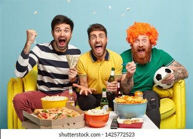 Friendship, game, gambling, leisure concept. Emotional excited three male friends watch football game on tv at home, clench fists, shout during goal, hold cash, pose on sofa, win on line bet
