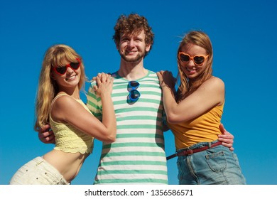 Friendship happiness summer holidays concept. Group of friends boy two girls in sunglasses having fun outdoor against sky